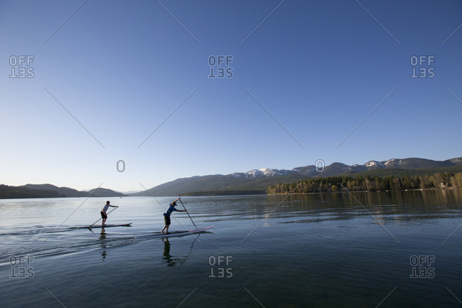 A fit male and female stand up paddle board at sunset on Whitefish Lake in Whitefish, Montana