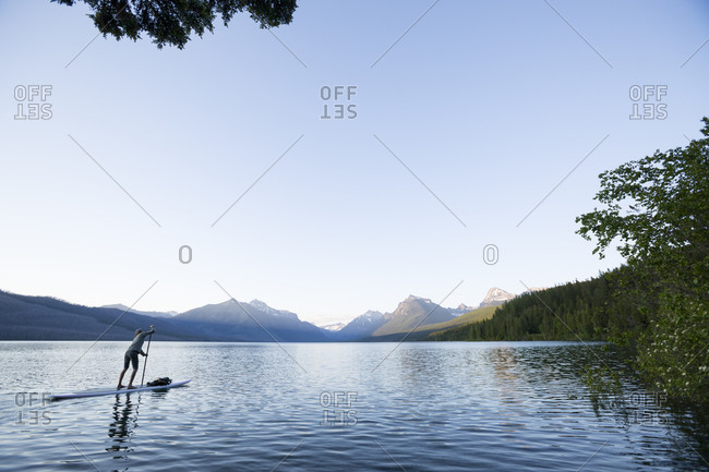 A woman up paddle boards (SUP) on Lake McDonald in Glacier National Park