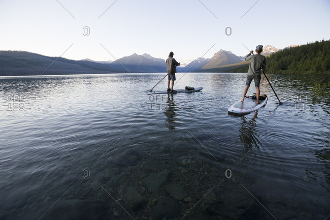 A man and woman stand up paddle boards on Lake McDonald in Glacier National Park