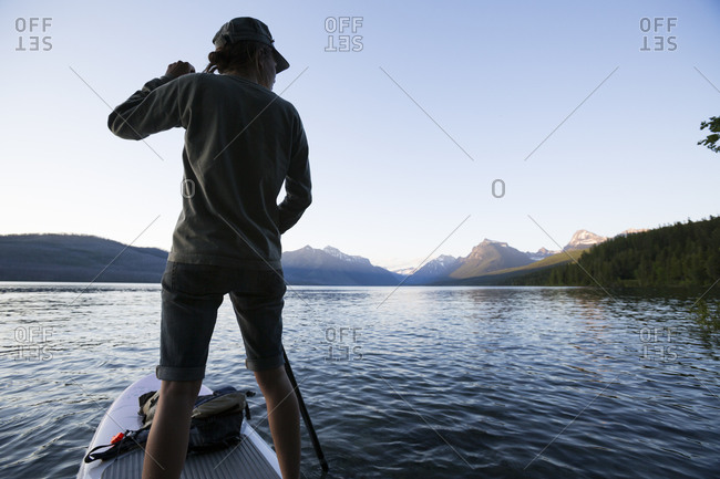 A woman stand up paddle boards on Lake McDonald in Glacier National Park
