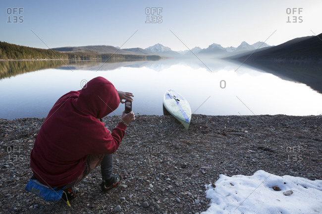 A man takes a photograph  of paddle boarding against Lake McDonald in Glacier National Park