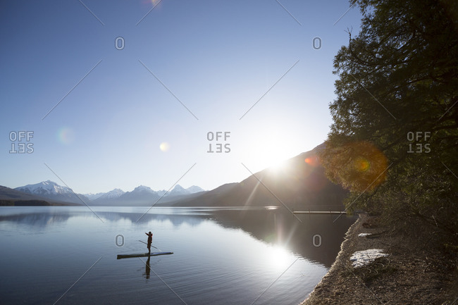 A man standing up on a paddle board, Lake McDonald in Glacier National Park