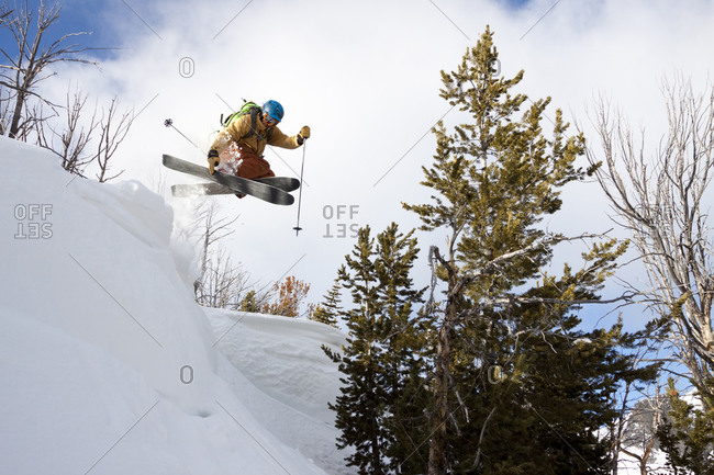 A male backcountry skier catches air off a cornice in the Beehive Basin near Big Sky, Montana