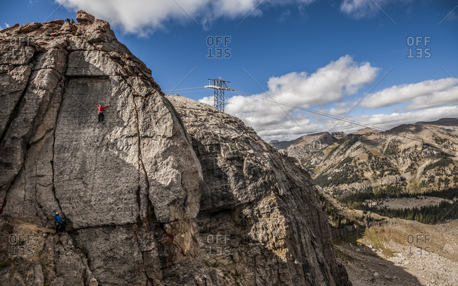 Two climbers while climbing a crag in Jackson Hole with the cable car cables and pylon in background Teton Village, Wyoming