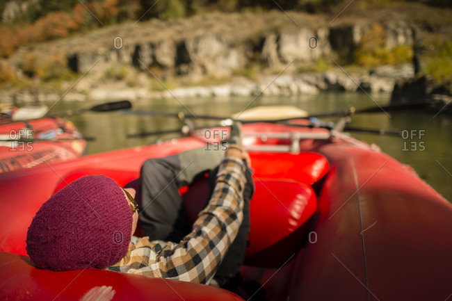 Man with cap, plaid shirt and sunglasses sleeping on a red boat along Snake River Jackson Hole, Wyoming
