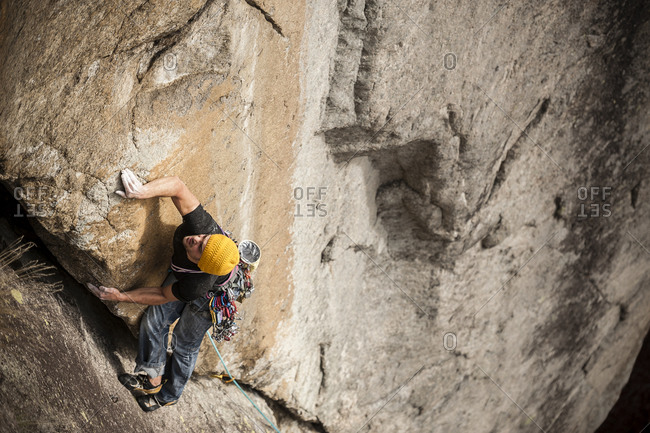 Man lead climbing a two pitches crack route in traditional style, Cadarese, Ossola Valley, Italy