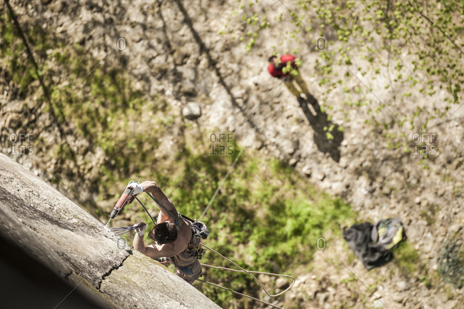 Rock climber bolting a new route in Premia's crag Premia, Piemonte, Italy