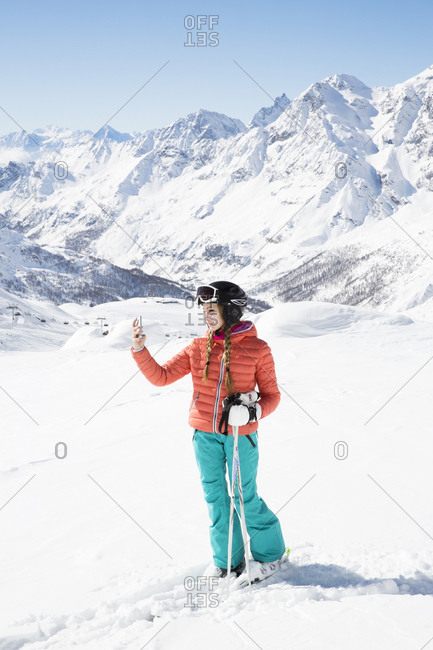 Young woman wearing skiwear taking picture with cell phone
