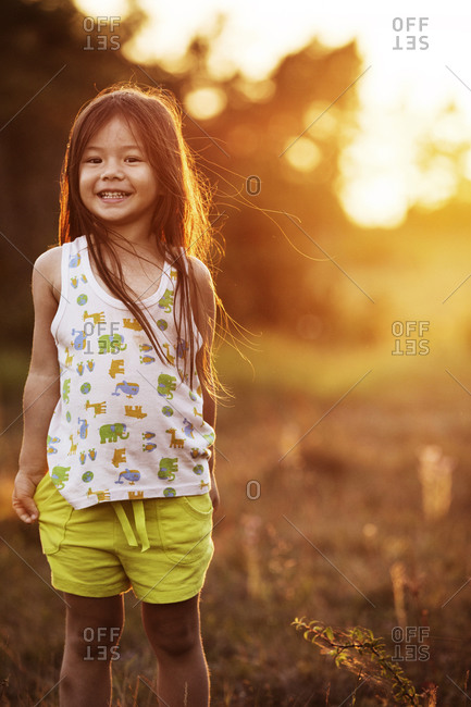 Girl smiling in a field at sunset