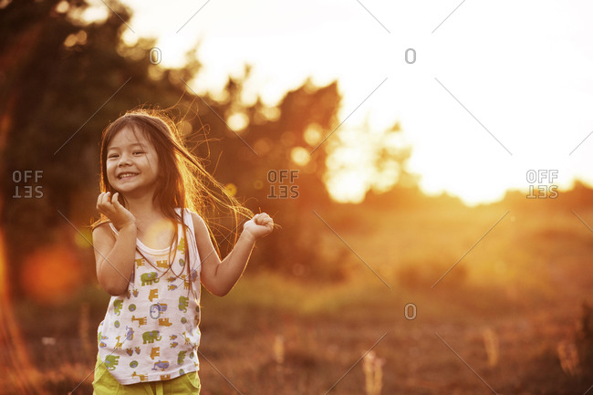 Girl giggling in a field at sunset