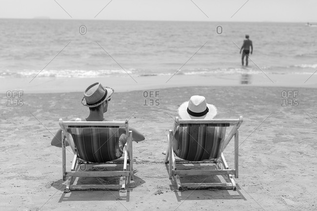 Smiling couple on lounge chairs