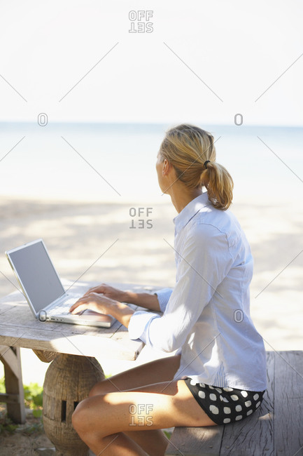 Young woman distracted by beach from work