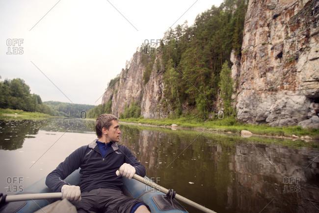 Man rowing down river near rocks in Oregon