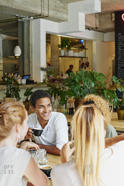 Man and friends laughing in coffee shop