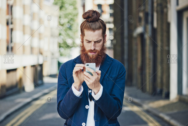 Man in sports coat in street looking at phone