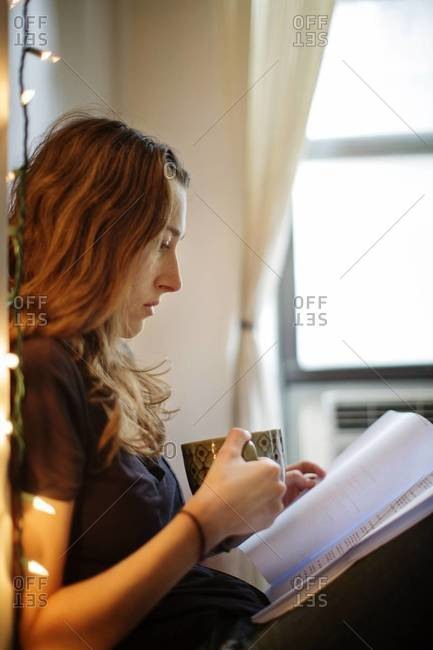 Woman reading script in bed with coffee