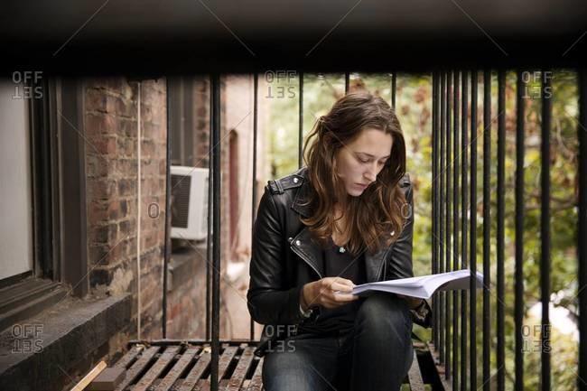 Woman on fire escape reading script