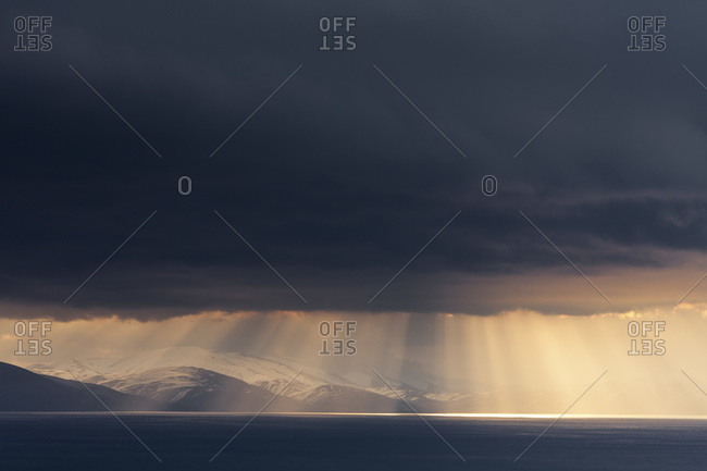 Sun rays break through clouds over the ocean