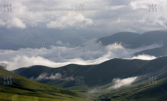 Clouds sweep through rolling green hills