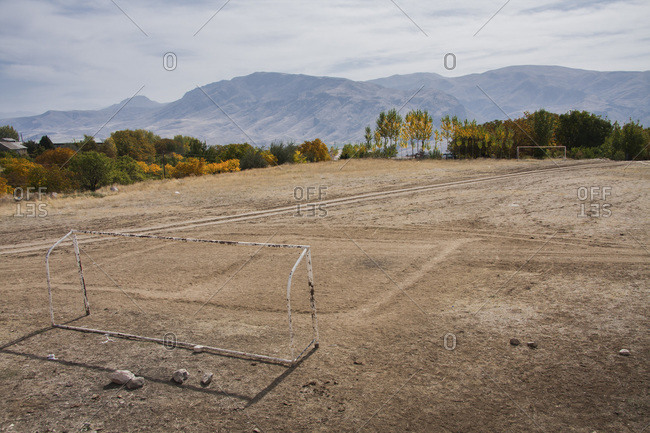 A run down soccer field in a mountainous landscape