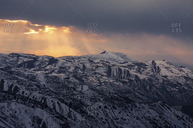 Sun rays shine on snow covered mountains
