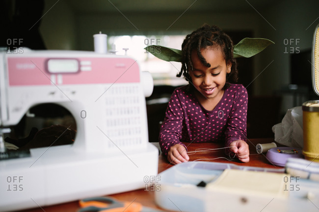 Girl by sewing machine with costume ears
