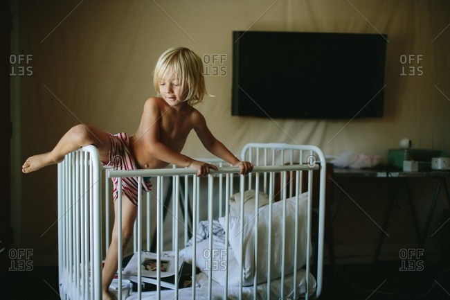 Little boy climbing out of his crib
