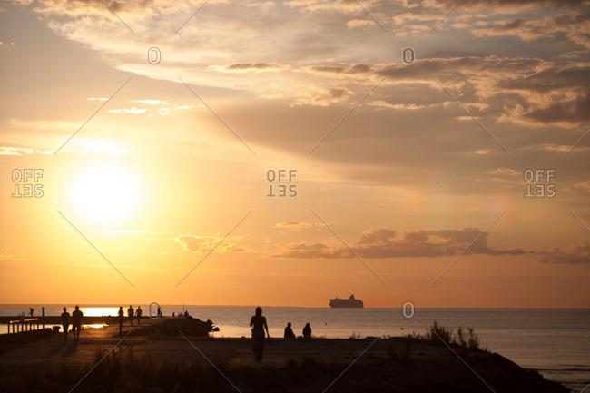 People on coastal walkway at sunset