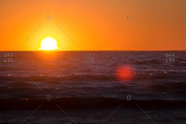 Orange setting sun over ocean