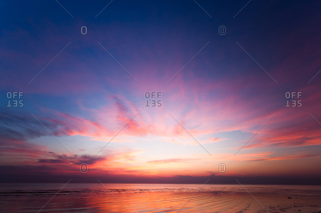 Colorful ocean sunset with blue sky