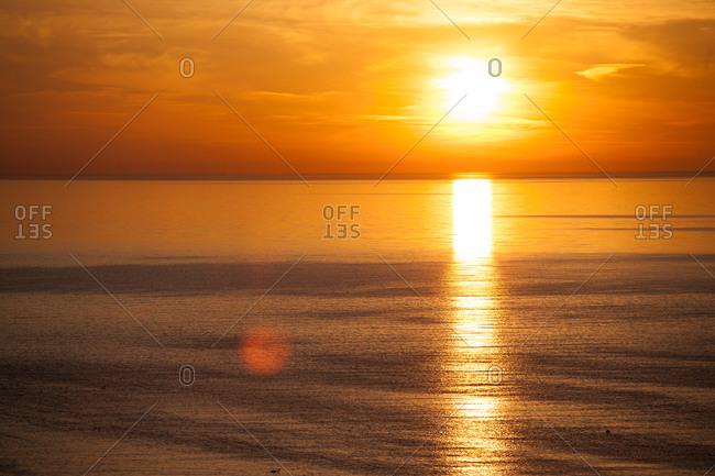 Sun setting low over ocean
