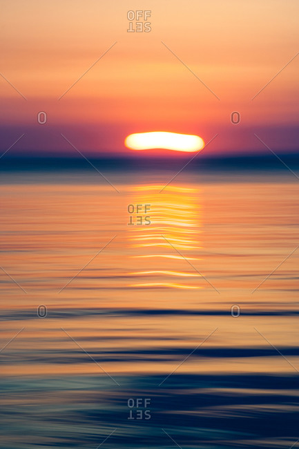 Sun dipping below sea horizon