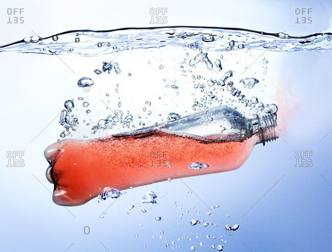 Bottle of red carbonated fruit beverage falling into water