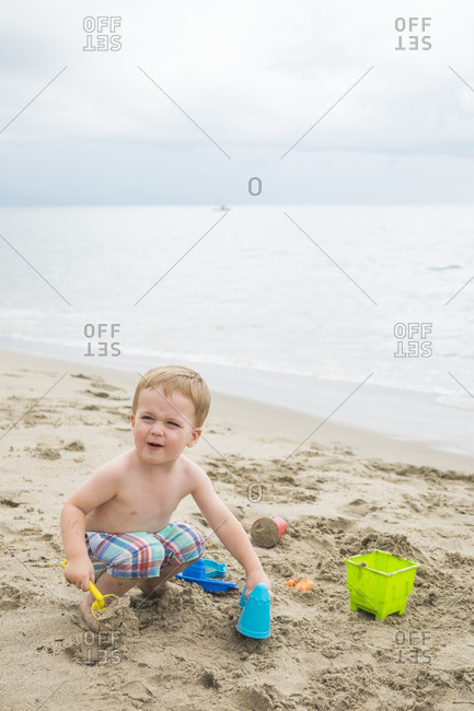 Toddler playing on the beach at seafront