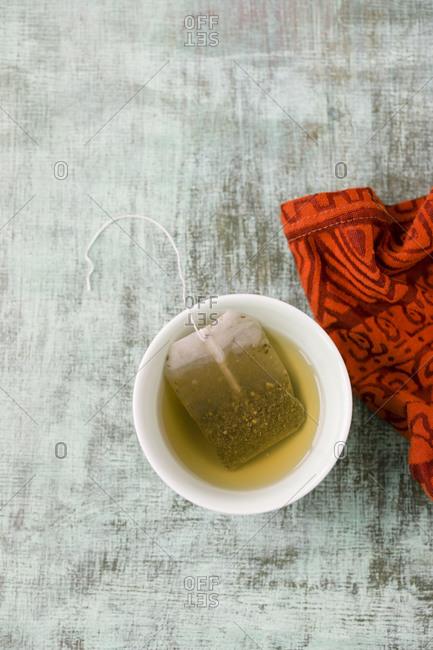 Bowl of Ceylon tea with tea bag on cloth