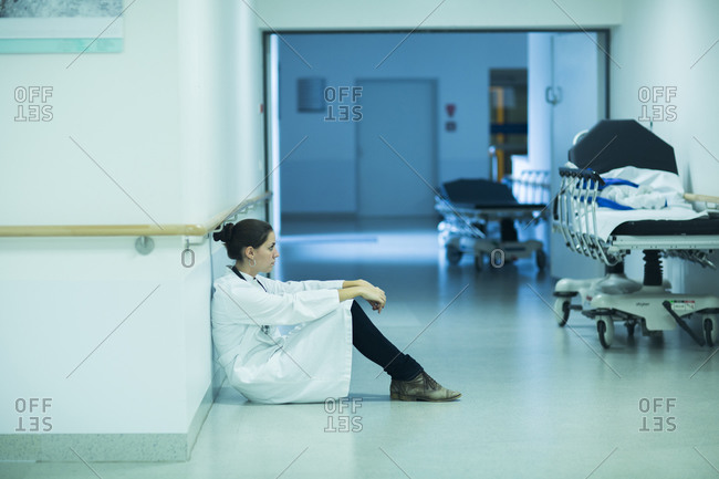 Overstressed young doctor sitting on hospital corridor