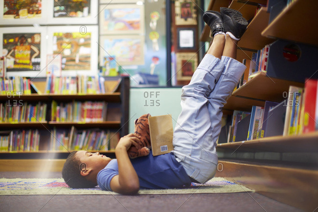 Boy lying on floor in library