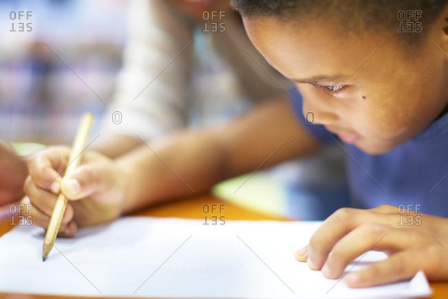 Young woman teaching boy writing on paper