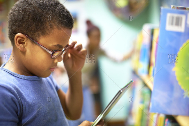 Boy in library holding digital tablet