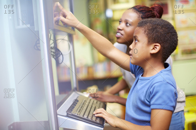 Young woman and boy using computer in library