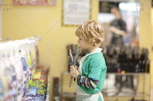 Boy painting in art class