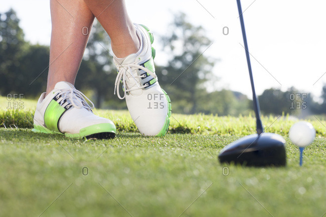 Legs of female golfer teeing off at a golf course