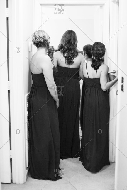 Bridesmaids stand in a doorframe