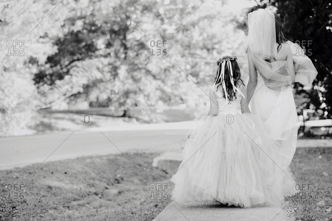 A flower girl walks with a bride