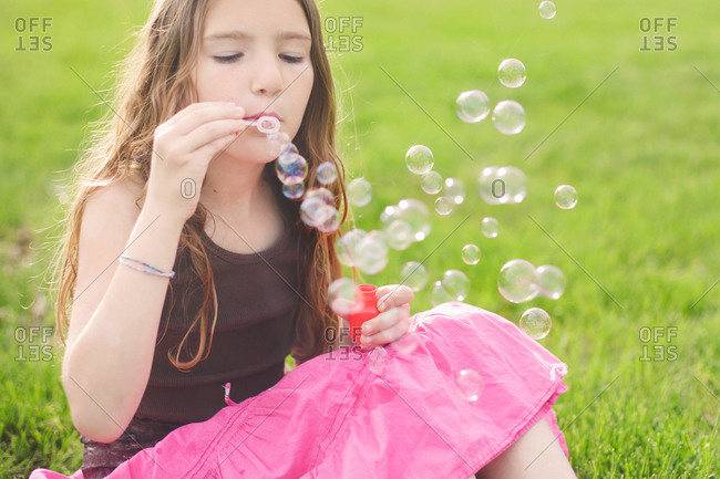 Girl blowing soap bubbles in garden