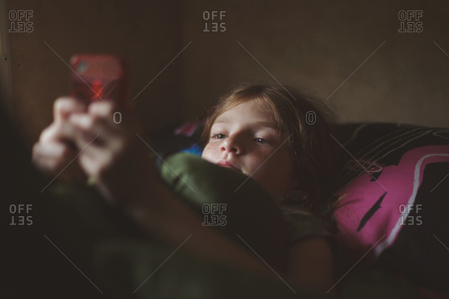 Girl using a smartphone in bed