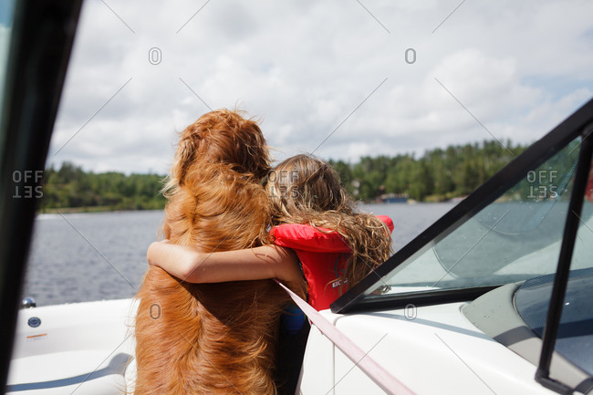 Young girl hugging a dog on a boat