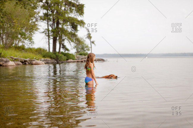 Young girl standing in a lake with a dog