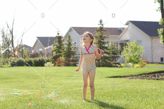 Young girl standing next to a sprinkler