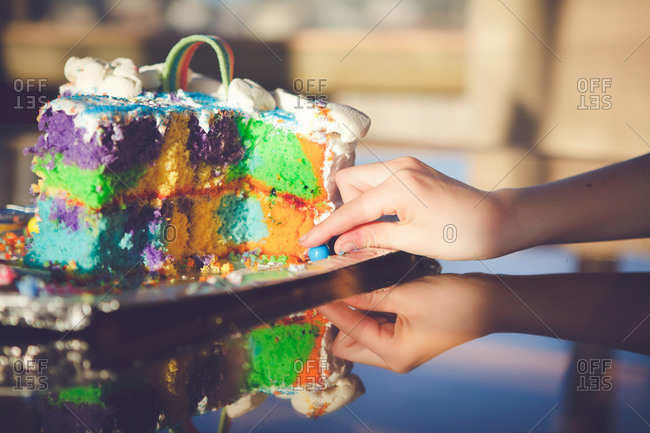 Child taking a candy from a rainbow cake